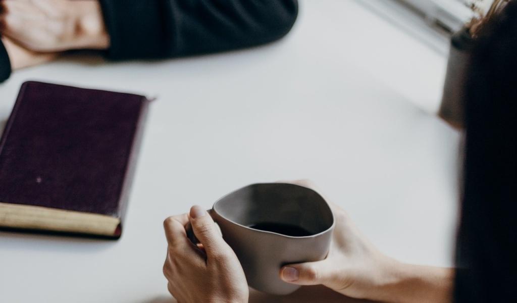 soft skills: uma mulher e um homem conversando enquanto tomam café segurando suas xícaras. Foto: Unsplash @Priscilla Du Preez