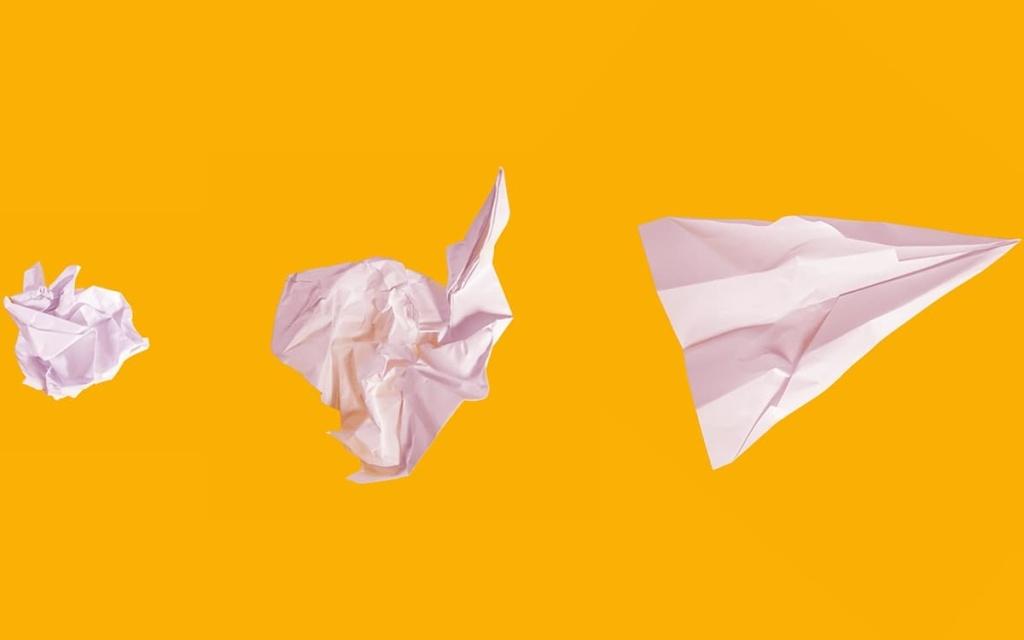 5 erros entrevista emprego: foto de papeis brancos amassados e formando um avião de papel progressivamente com fundo amarelo. @mattwridley/Unsplash