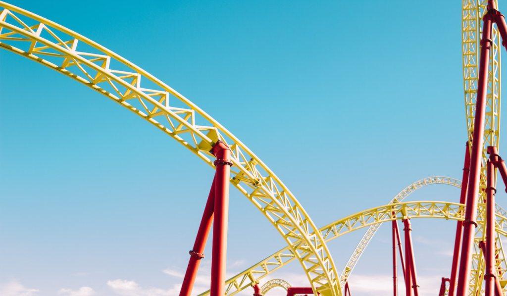 Bitcoin o que está acontecendo: fotografia de uma montanha-russa amarela e vermelha com o céu azul ao fundo