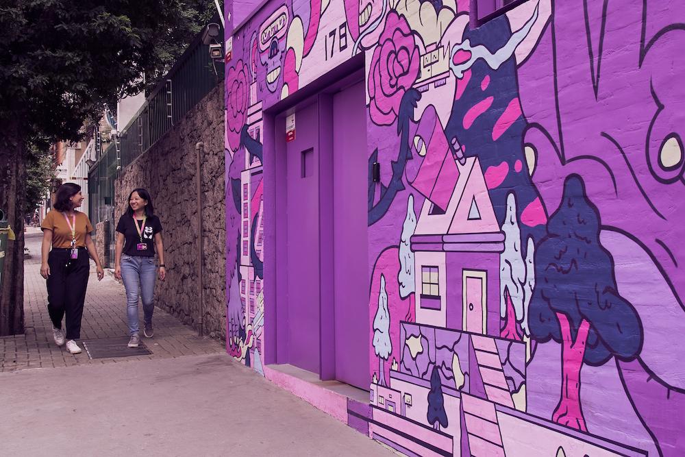 Fachada de uma casa toda grafitada com imagens roxas. Duas mulheres vêm pela calçada conversando e sorrindo.