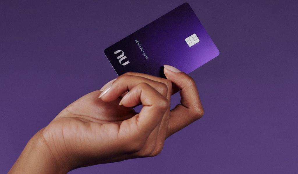 Nubank Ultravioleta Cartão Virtual: fotografia de uma mão segurando o cartão Nubank Ultravioleta com um fundo roxo escuro atrás