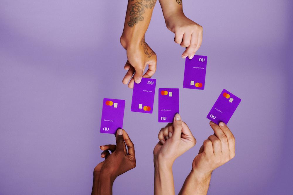 Cinco mãos aparecem segurando cartões Nubank. Três aparecem por baixo segurando o cartão pra cima e duas aparecem de cima segurando o cartão pra baixo.