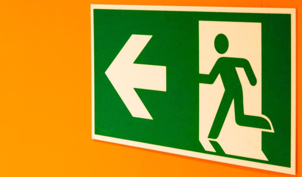 golpes entrevista de emprego: imagem de placa de saída de emergência com fundo laranja. Unsplash/ @moino007