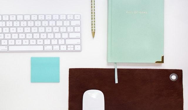 Imagem de uma mesa com um teclado de computador branco ao lado de um lápis amarelo e um caderno verde pastel.