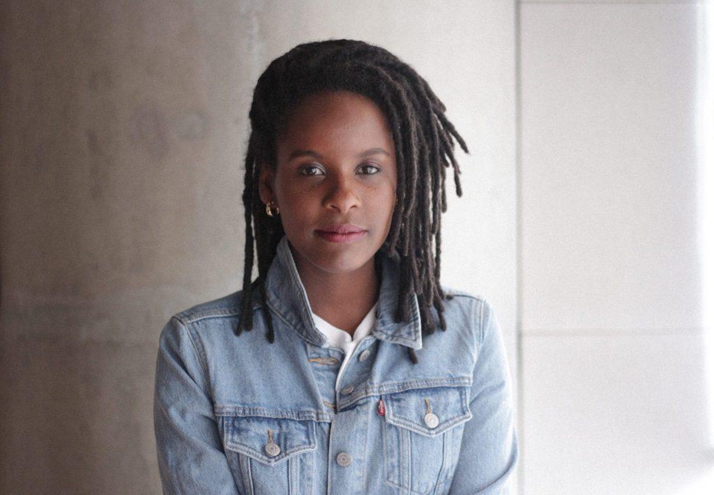 A influenciadora Monique Evelle, uma mulher negra, jovem, de tranças, aparece de frente para a câmera esboçando um leve sorriso