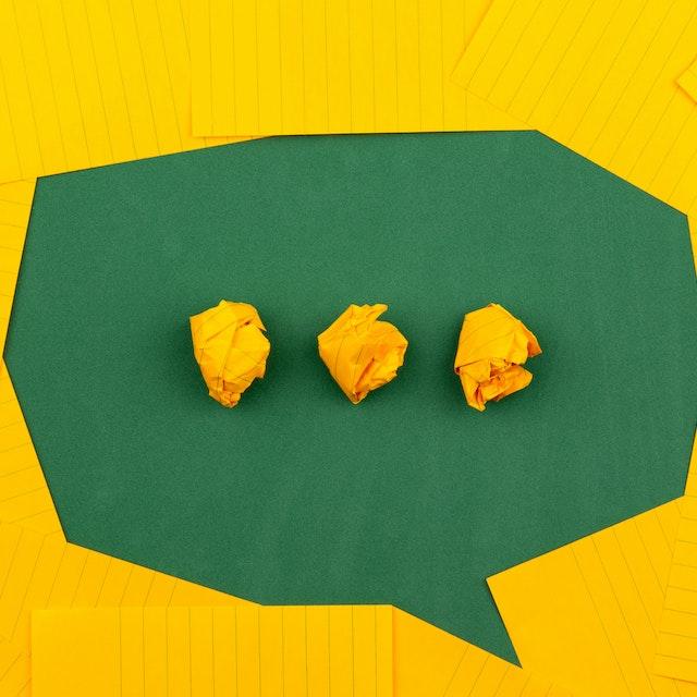 Pix poderá ser usada em aplicativos de mensagem: cartões amarelos dispostos formando um balãozinho de conversa verde no meio. Ao centro, três bolinhas amarelas de papel. Créditos da imagem: Volodymyr Hryshchenko