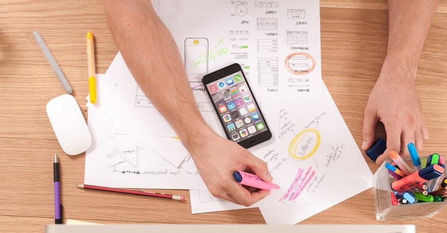 Vista de cima de uma pessoa organizando vários papeis e documentos, com uma caixa de canetas coloridas ao lado. Foto via Unsplash