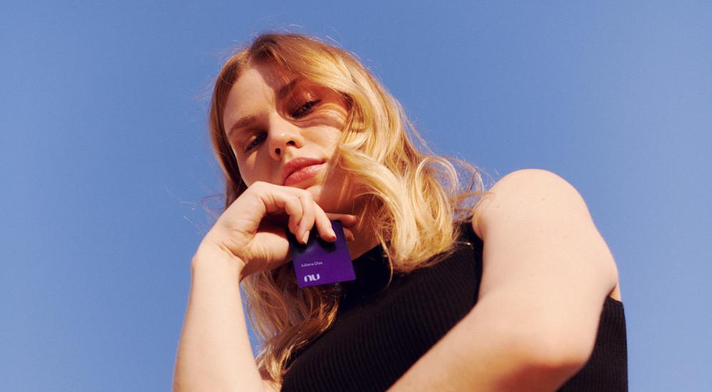 Foto de uma mulher tirada a partir de um ângulo mais baixo que ela. Ela está olhando para a câmera, série, segurando um cartão Nubank Ultravioleta perto do rosto.