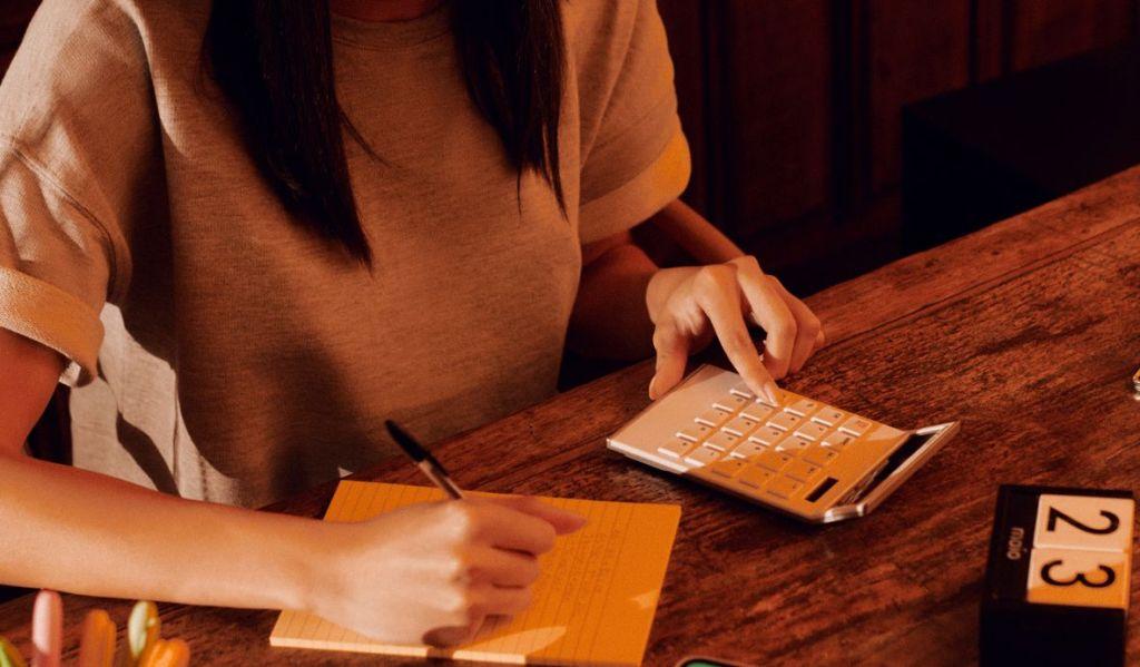 mulher faz cáculos na calculadora e anotações em um caderninho sentada em uma mesa de escritório