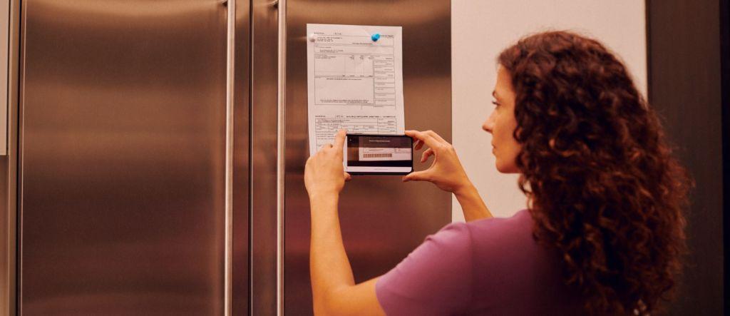 Mulher de cabelos longos e en aracolados vestindo uma camiseta roxa aponta o celular para um boleto que está fixado na porta da geladeira