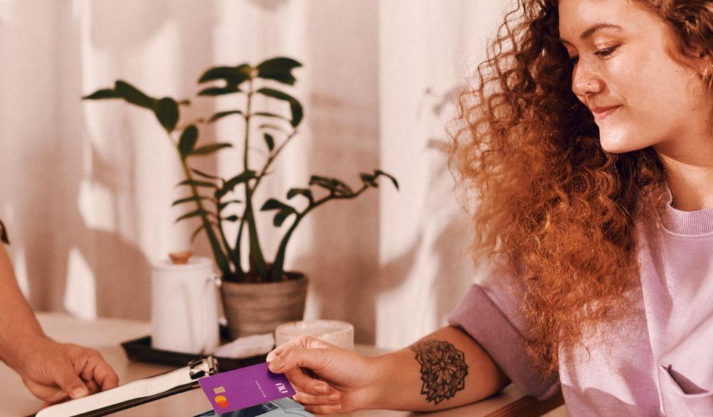 mulher ruiva e tatuada fazendo um pagamento por maquininha a homem de meia idade empreendedor