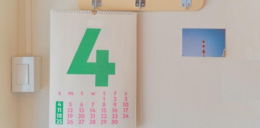 Imagem de um calendário de parede com papel branco, letras rosas e um número 4 verde bem grande, ocupando mais da metade do espaço. Foto via Unsplash.