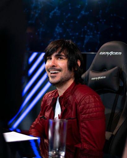 Como transformei minha paixão por games em carreira: fotografia de Henrytado em um estúdio. Ele está olhando para frente e sorri.