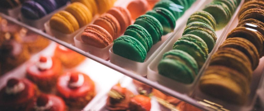 Vários biscoitos coloridos em várias fileiras num balcão, com doces ao fundo