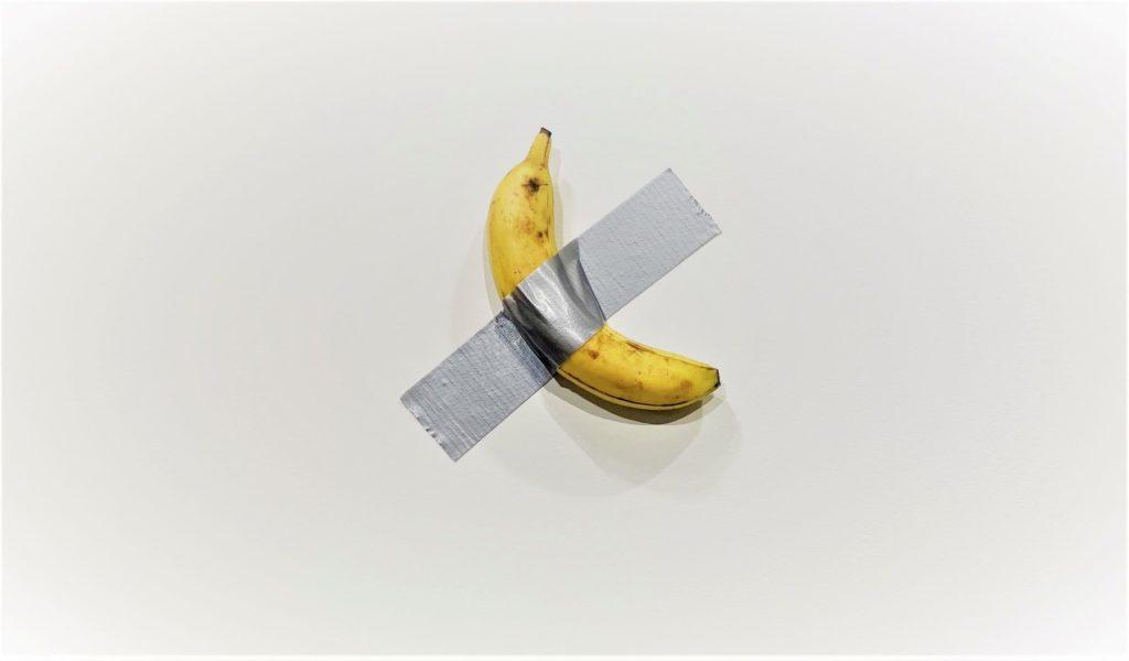 Em uma parede branca, uma banana está fixada com um pedaço de silver tape, uma fita adesiva prateada