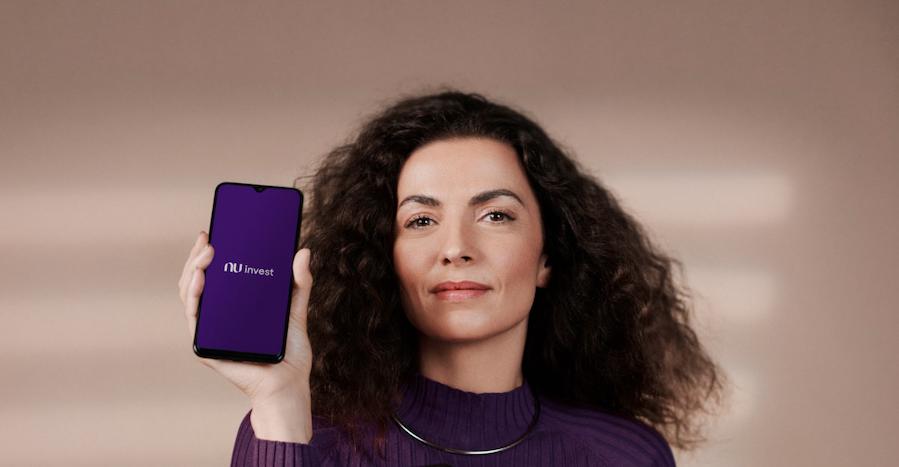 Foto de uma mulher de cabelo cacheado usando um casaco roxo. Ela está segurando um celular com a tela inicial do app Nu invest