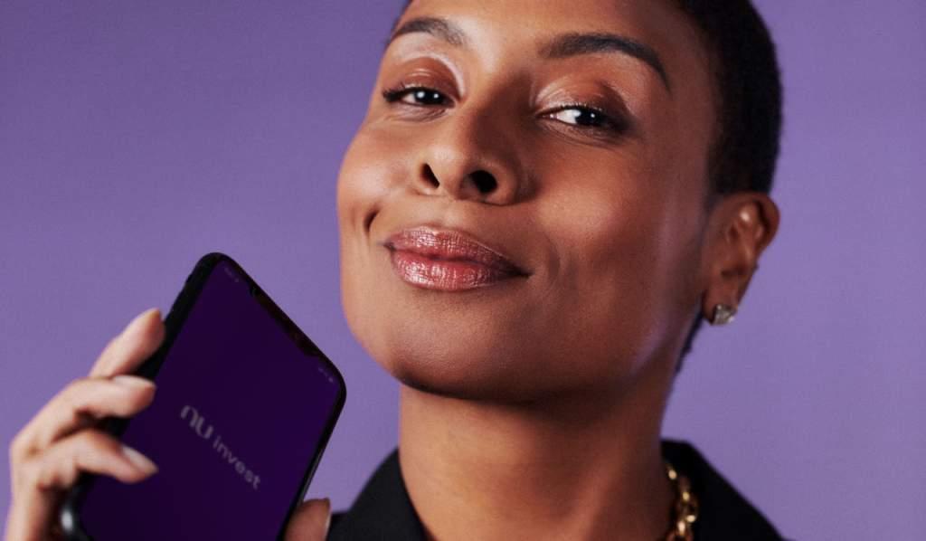 Foto de uma mulher sorrindo para a câmera enquanto segura um celular com a tela virada para frente. Na tela está o logo Nu invest