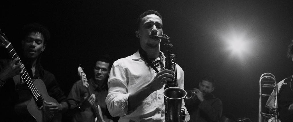 Propaganda Nubank, a história de Lucas: fotografia em preto e branco de Lucas tocando saxofone com os olhos fechados. Ao fundo, outras pessoas tocam outros instrumentos musicais, como uma guitarra e um clarinete.
